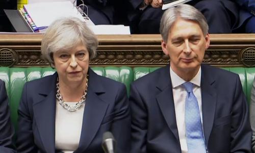 A video grab from footage broadcast by the UK Parliament's Parliamentary Recording Unit (PRU) shows British Prime Minister Theresa May (L) and British Chancellor of the Exchequer Philip Hammond as they listen to a speaker during Prime Minister's Questions (PMQs) in the House of Commons in London on March 15, 2017. Prime Minister Theresa May said Tuesday she would be given the power to start Brexit talks within days but declined to name a date for a process already disrupted by Scotland's independence bid. / AFP PHOTO / PRU AND AFP PHOTO / HO / RESTRICTED TO EDITORIAL USE - MANDATORY CREDIT