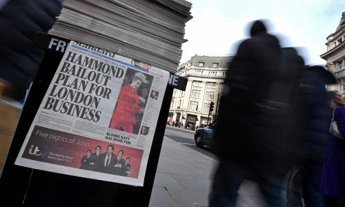 Pedestrians walk past an Evening Standard newspaper distributor, with the paper's main headline referring to British Chancellor of the Exchequer Philip Hammond's budget plans, on Regent Street in central London on March 6, 2017. British Chancellor of the Exchequer Philip Hammond has said he will keep chopping away at the deficit to get Britain fit to face Brexit, as he prepares to deliver his budget on March 8. / AFP PHOTO / BEN STANSALLBEN STANSALL/AFP/Getty Images