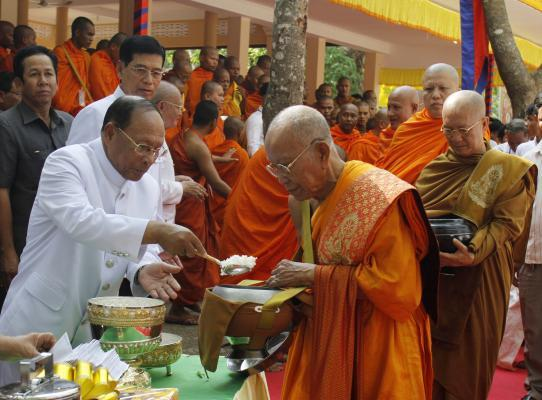 Bour Kry (kanan, jubah coklat), menerima dana makanan dari Ketua Parlemen Kamboja, Heng Samrin, dalam perayaan Hari Vesak 2559 EB di Gunung Phnom Oudong, Sabtu (2/5/2015)