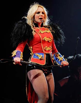 Inspired by a lion tamer (complete with leather whip), Britney takes the stage in a sexy red ringmaster coat, tall lace-up boots, and not much else. - Kevin Mazur/WireImage.com