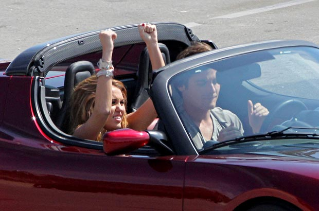 Miley goes for a ride in a $129,000 red Tesla roadster. - Carrillo/PacificCoastNews.com