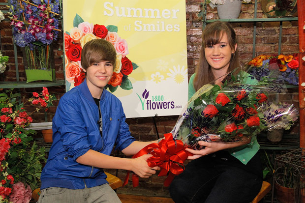 "Justin Bieber presents the ""One Less Lonely Girl"" flowers to a lucky fan. - Randy Brooke/WireImage.com"