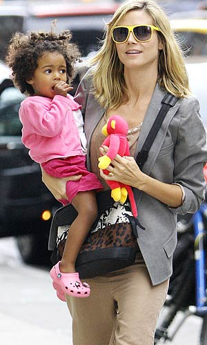 Heidi keeps her youngest kiddie, 20-month-old Lou, entertained with a toy. - Saleem & Ahmad Elatab/Splash News