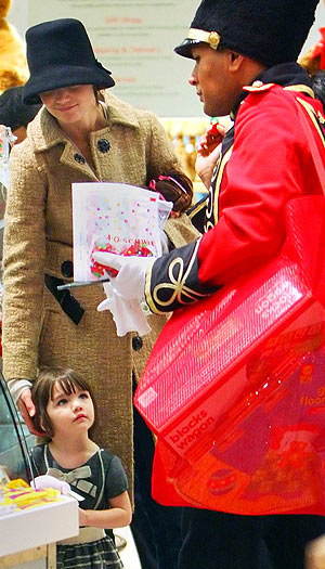 A friendly toy soldier steps in to help Katie and Suri with all their stuff! - Jackson Lee/Splash News