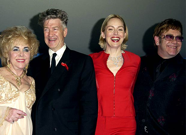 Dame Elizabeth Taylor with director David Lynch, Sharon Stone, and Sir Elton John at amfAR's Cinema Against AIDS Gala in Cannes, 2002. - J. Vespa/WireImage