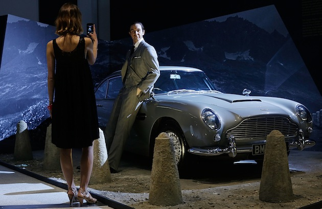 "An employee poses in front of a Sean Connery wax figure and the famous Aston Martin DB5 at the Barbican Center's new ""Fifty Years of Bond Style"" exhibition. (Photo by Matthew Lloyd/Getty Images)"