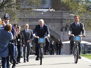 Mayor of London Boris Johnson (L) cycled on London Cycle Hire bikes with Arnold Schwarzenegger in front of City Hall in 2011 when the two met to discuss low- and zero-emission technologies. (Photo by Fred Duval/Getty Images)