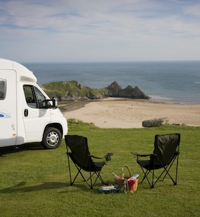 A caravan site ready for lunch on top of a cliff overlooking Three Cliffs Bay on the Gower peninsula in Wales. (Photo by Rod Edwards/Visit Britain)