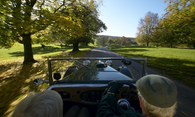 A man and a woman drive a classic car through the Chatsworth Estate amid the landscape of Derbyshire's Peak District National Park, England. (Photo by Daniel Bosworth/Visit Britain via East Midlands Tourism)