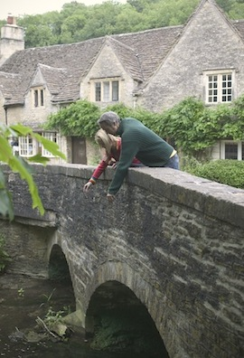 A couple plays Pooh Sticks in Castle Combe, a village in Wiltshire, England. (Photo by Martin Brent/VisitBritain)