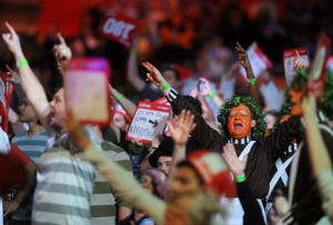 Darts competitions are raucous events where fans dress up in costume and wave signs for their favorite competitors. (Photo by Charlie Crowhurst/Getty Images)