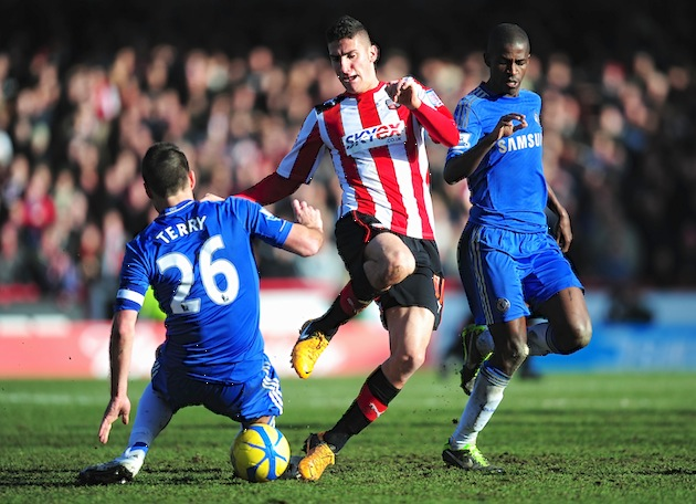 Marcello Trotta of Brentford is tackled by John Terry of Chelsea during the FA Cup Fourth Round match between Brentford and Chelsea in Brentford, England. The teams tied and will play again this weekend. (Photo by Jamie McDonald/Getty Images)