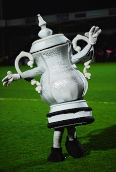 The FA Cup mascot, modeled after the FA Cup trophy with its distinctive large handles, entertains fans before a match. (Photo by Stu Forster/Getty Images)