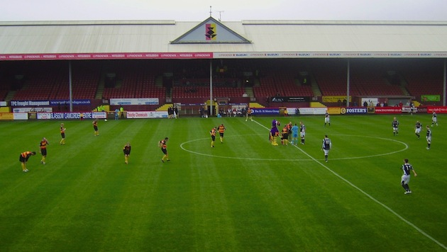 Partick Thistle F.C. (in yellow) warms up for a match at Firhill Stadium in Glasgow, one of many intimate venues of the Scottish Football League. (Photo by Big Jim Fae Scotland at via Wikimedia Commons)