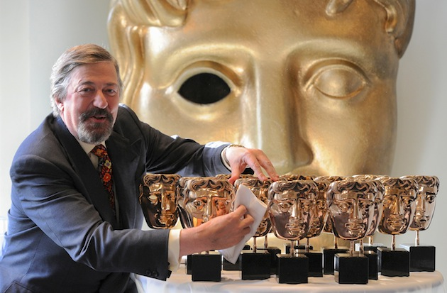 Host Stephen Fry playfully polishes statuettes in advance of the British Academy Film Awards. (Photo by Dave J Hogan/Getty Images)