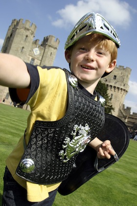 A boy dressed-up as a Knight in the Courtyard of Warwick Castle in central England. (Photo by Martin Brent/Visit Britain)