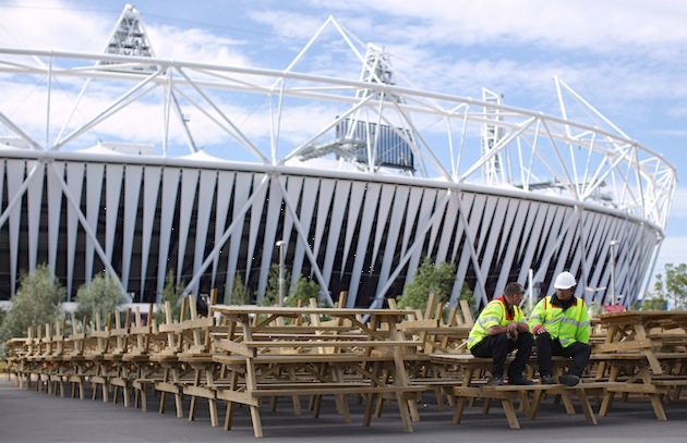 Workers take a break on a row of upturned benches outside the Olympic Stadium in in London. As the site redevelopment takes shape, the athletes village and sports venues will be transformed into new neighborhoods, leisure centers and visitor attractions. (Photo by Dan Kitwood/Getty Images)