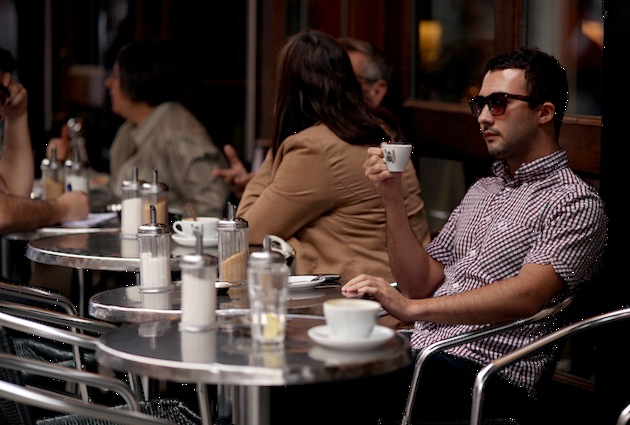 A man enjoys a cup of coffee in a cafe in the Soho area of the City of Westminster, London. (Photo by Oli Scarff/Getty Images)