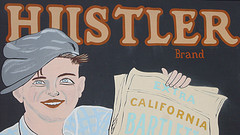 An antique sign with a news carrier and the word 'Hustler' at Casa de Fruta