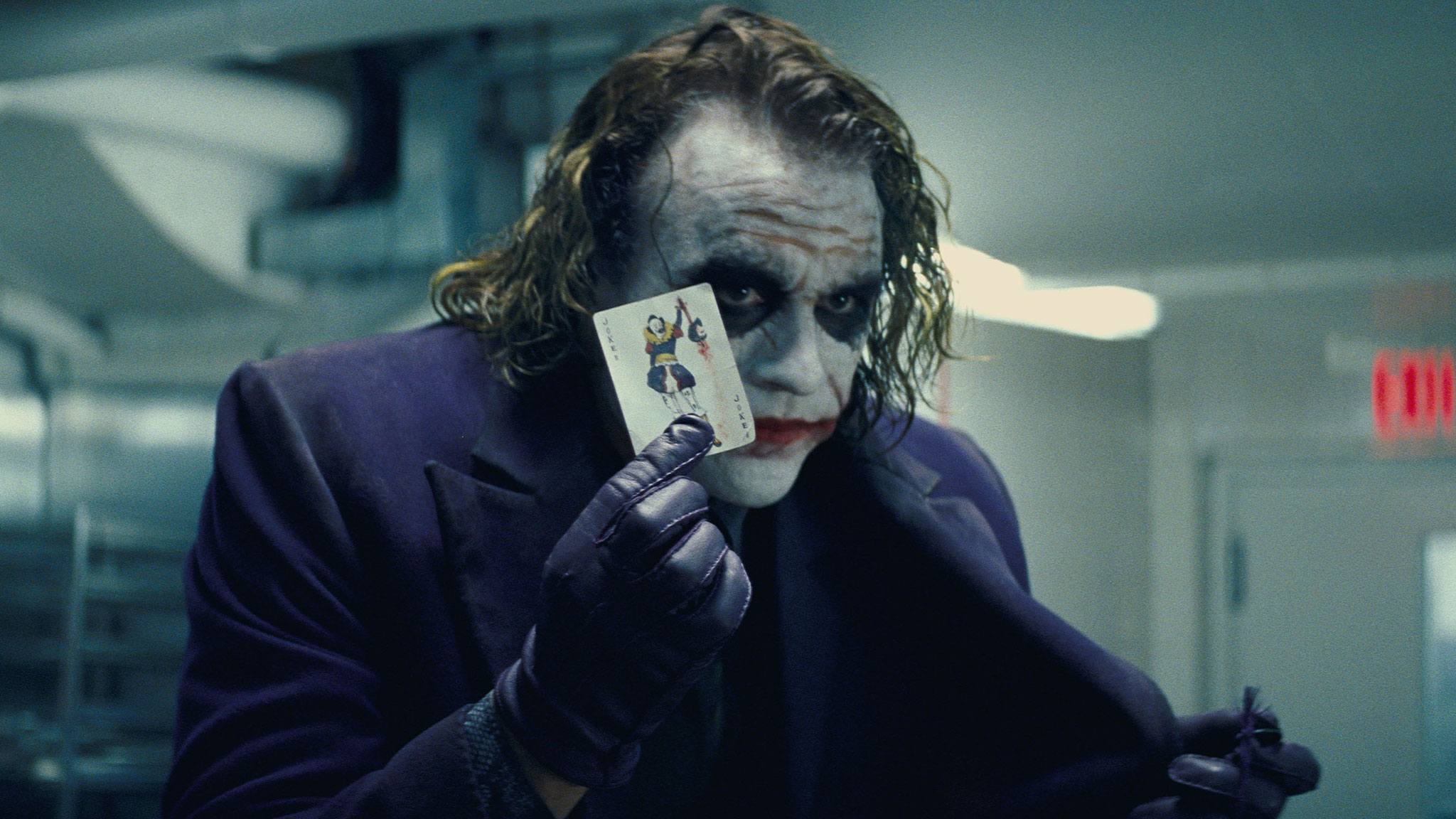 "Heath Ledger Holds Up a Joker Card in ""The Dark Knight"" (Photo Credit: Warner Bros.)"