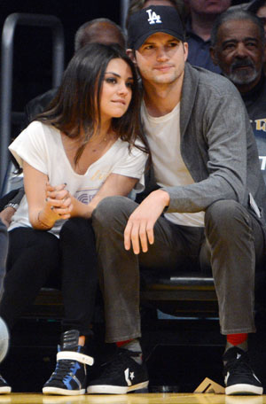 Mila Kunis and Ashton Kutcher cuddle at the Lakers (Splash News)