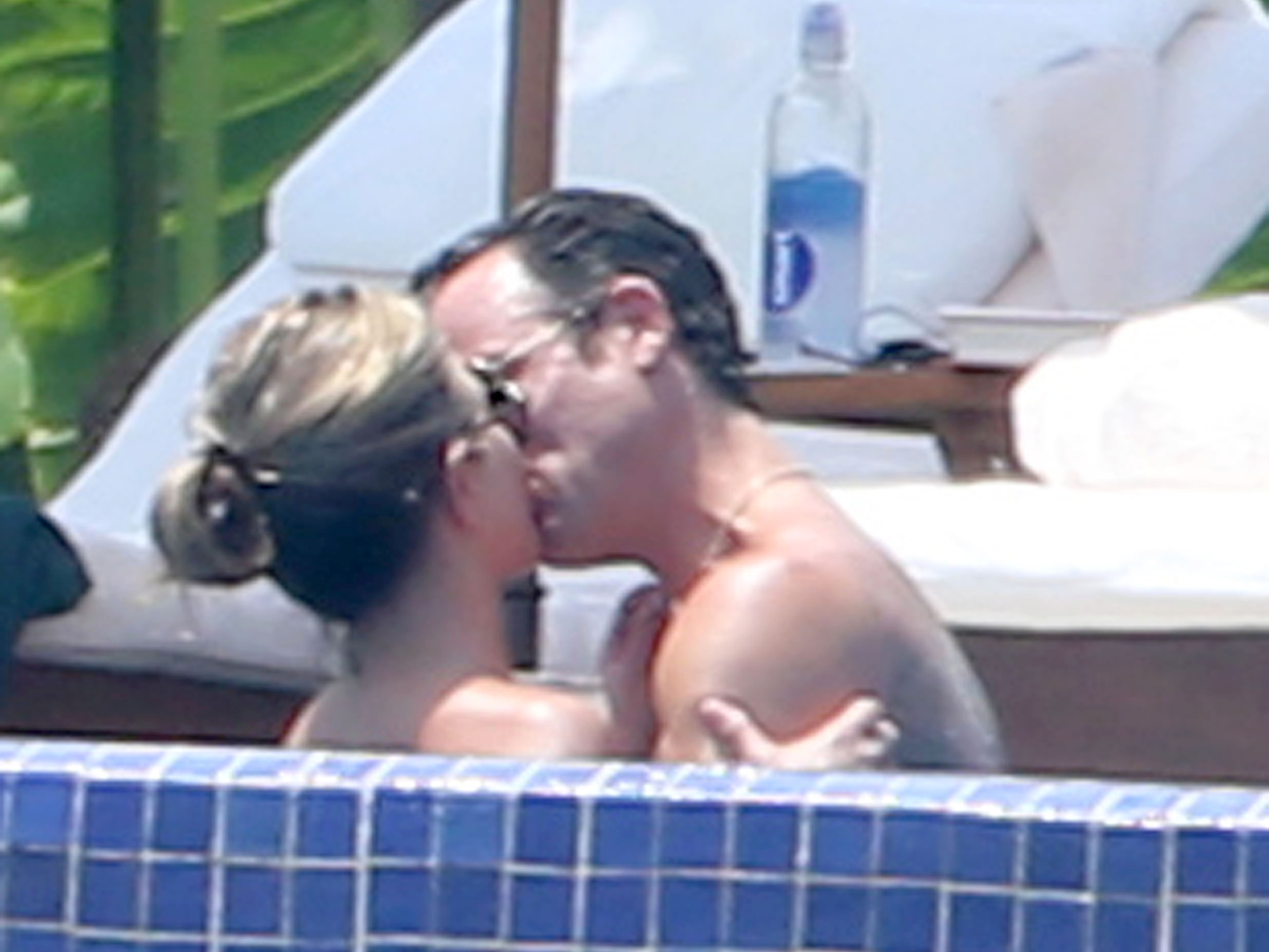 Aniston and her fiancé, Justin Theroux, kiss in the pool (FameFlynet)