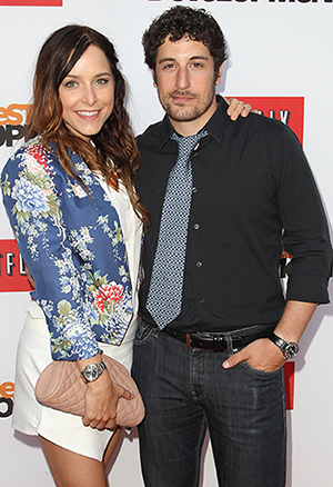 Jason Biggs and his wife, Jenny Mollen, pose on a red carpet. (Getty Images)