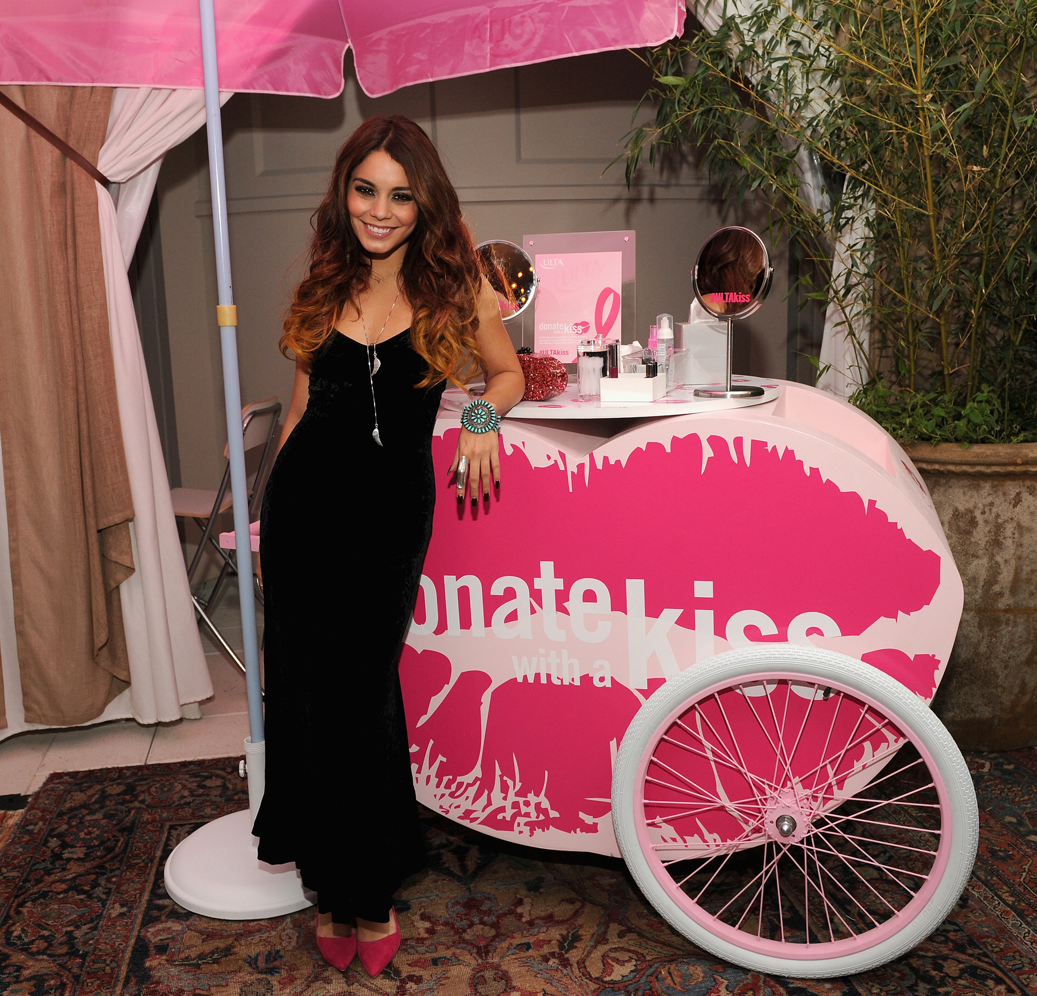 Hudgens posing at the Kiss Kart. (Getty Images)