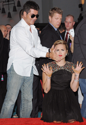 Cowell goofs with Lovato while making handprints at Grauman's Chinese Theatre (Getty Images)