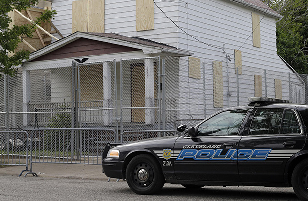A patrol car in front of Ariel Castro's boarded-up home in Cleveland (Mark Duncan/AP)