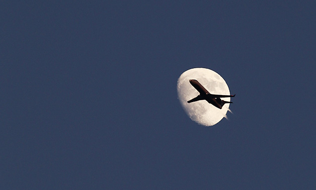An airplane flies in front of the moon (Gary Hershorn/Reuters)