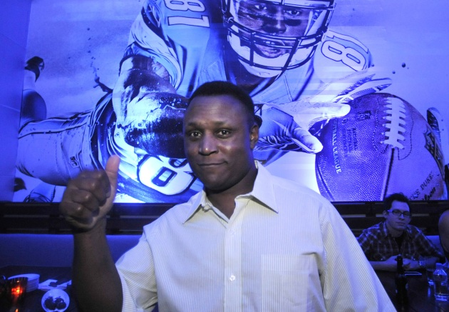 Barry Sanders posing in front of Madden 13 (Credit: Getty Images)