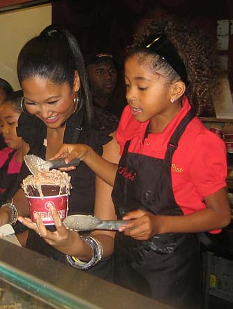 Kimora lends Aoki a hand as she works on her masterpiece. - Cold Stone Creamery