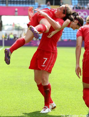 Canada's Rhian Wilkinson picks up Diana Matheson in celebration of Matheson's goal.