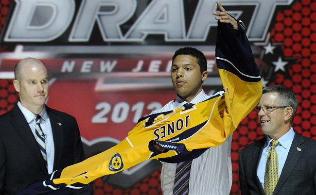 Seth Jones accepts a Nashville Predators sweater after going No. 4 overall on Sunday (The Associated Press)