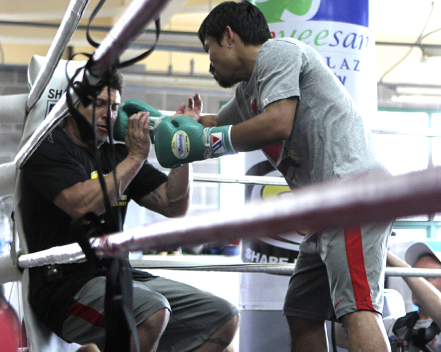 Manny Pacquiao (R) playfully punches strength & conditioning coach Alex Ariza (AP)