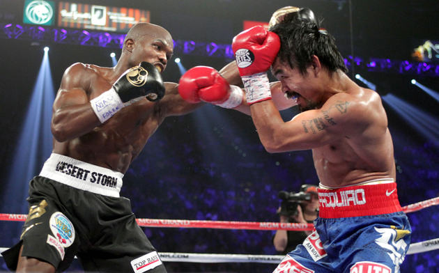 Timothy Bradley and Manny Pacquiao exchange punches on June 9 (Chris Farina/Top Rank)