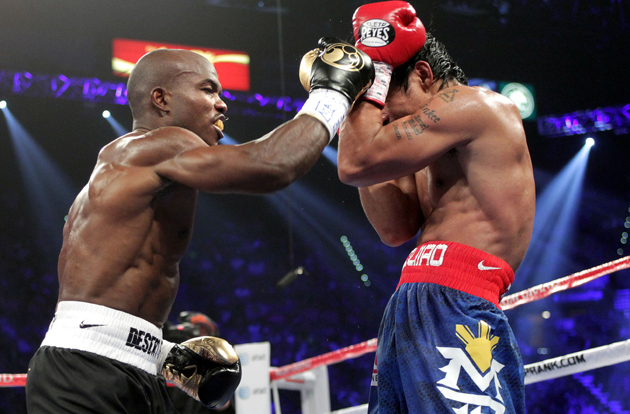 Manny Pacquiao (R) blocks a punch from Timothy Bradley (Chris Farina/Top Rank)