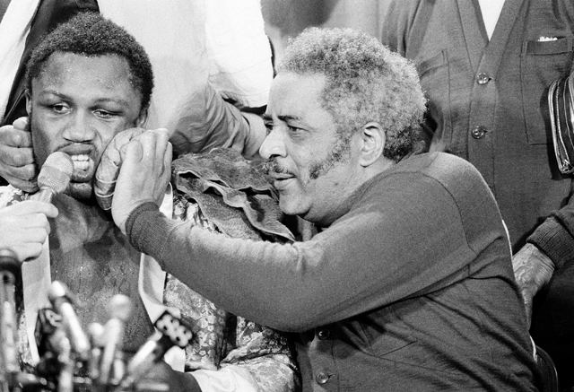 Trainer Yancey Durham (R) applies an ice pack to Joe Frazier's face on March 8, 1971 (AP file photo)