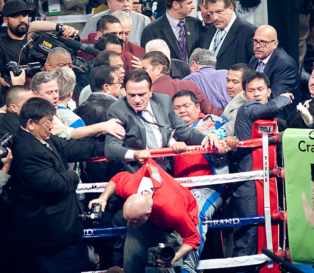 Michael Koncz (grey suit) grabs photographer Al Bello's shirt as Buboy Fernandez kicks at him (Chris Cozzone)