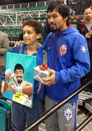 Cancer patient John Rocero (L) presents a painting to Manny Pacquiao (Kevin Iole)