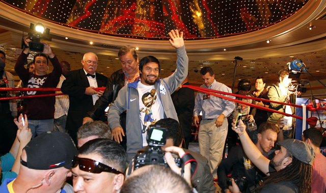 Manny Pacquiao waves to fans after his arrival at the MGM Grand on Tuesday (Chris Farina/Top Rank)