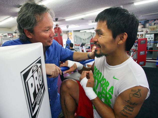 Boxer Manny Pacquiao (R) speaks with Pastor Jeric Soriano before a training session (Chris Farina/Top Rank)
