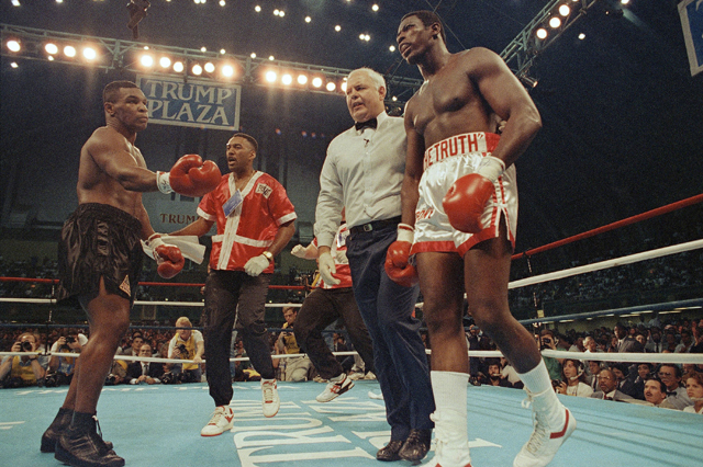 Carl Williams (R) walks to his corner after being stopped by Mike Tyson. (AP)