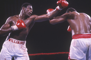 Williams (L) fought Larry Holmes for the title in 1985. (Getty)