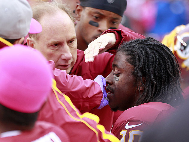 Robert Griffin III receiving treatment, post-hit (US Presswire)