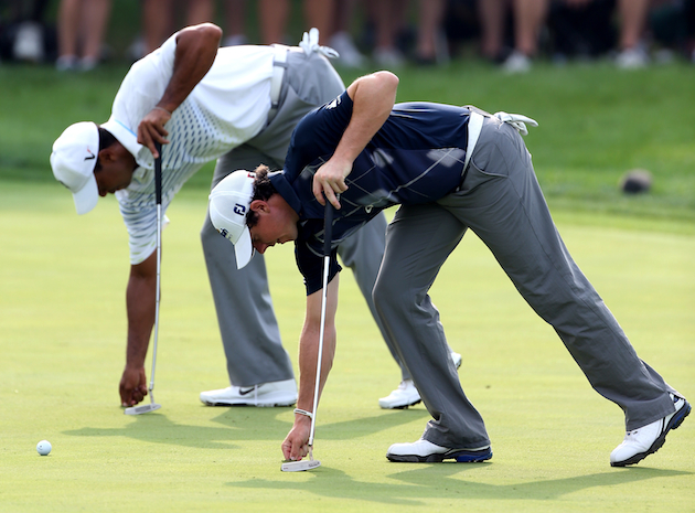 Rory McIlroy and Tiger Woods do their best synchronized putting routine. — Getty Images