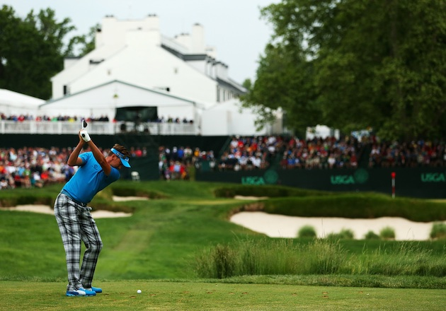 Ian Poulter tees off on the 13th during Thursday's Round 1. (Getty Images)
