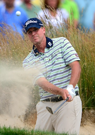 Steve Stricker hits out of a bunker on No. 4. (Getty Images)