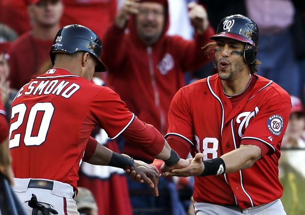 Ian Desmond and Michael Morse celebrate Tyler Moore's big hit. (AP)
